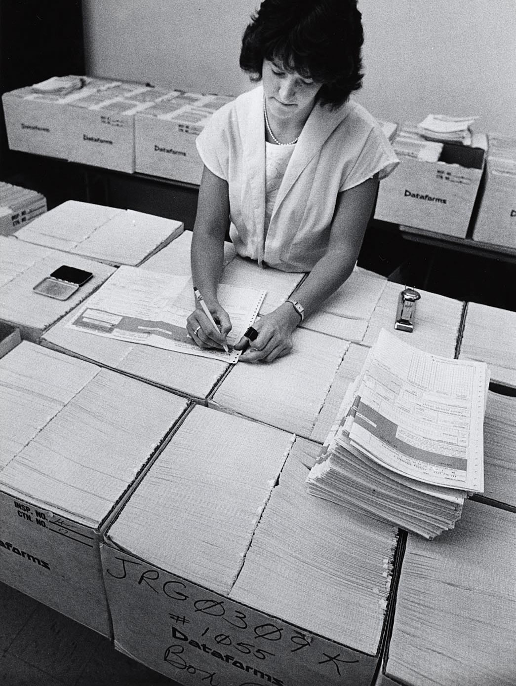 1980s photo of student with many boxes of paper registration forms.